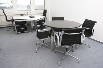 White table in an office with balck chairs.